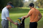 picture of golf bag  - Young men standing in golf course by golf bag full of sticks - JPG