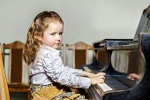 stock photo of grand piano  - Cute little girl playing grand piano in music school childhood concept - JPG