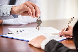stock photo of rental agreement  - Young woman is signing financial contract with male realtor - JPG