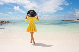 foto of yellow  - Fashionable woman with black summer hat and yellow dress on the beach - JPG