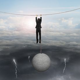 stock photo of shackles  - Businessman shackled by heavy concrete ball hanging on the rope with opposite weather conditions sky background bright sun cloudscape and dark cloudy lightning - JPG