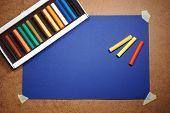 Leere blaue Karton-Hintergrund und mehrfarbige Pastel - Kunst-Utensil