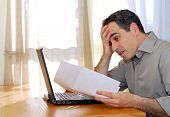 picture of single man  - man sitting at a desk looking at bills with horror - JPG