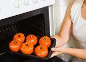 Cook  Putting Farci Tomato Into Oven