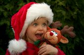 stock photo of santa-claus  - portrait of a baby girl wearing santa claus hat with reindeer toy - JPG