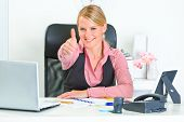 Smiling modern business woman sitting at office desk and showing thumbs up gesture