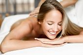Young Blonde Woman Having Massage And Smiling In The Spa poster