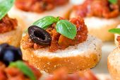 stock photo of italian food  - The perfect Italian appetizer fresh bruschetta with basil and olives - JPG