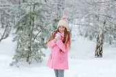 Adorable smiling girl playing with the snow in the winter snow-covered woods poster