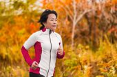 Active woman running and jogging. Middle aged Asian mature female jogger outdoor living healthy life poster
