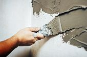 Painting Worker Puttied Wall Using A Paint Spatula Hand Closeup. poster