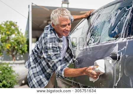 poster of Happy senior man washing car with soap and foam. Old retired man cleaning automobile with sponge in