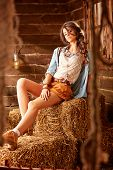 Romantic Young Hippy Posing In A Barn Sitting On A Hay poster