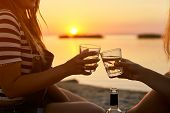 Women Clink Glasses With White Wine On The Beach. Girlfriends Cheerfully Celebrate Vacation And Proc poster