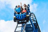 Young family having fun riding a rollercoaster at a theme park. Screaming, laughing and enjoying a f poster