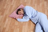 Young man dress with nightclothes sleeping on the floor (isolated on white)