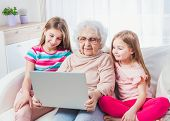Great-grandmother with granddaughters watching laptop together poster