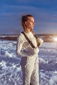 A Woman In A White Jumpsuit In Winter Outside, Background Is Snow Drifts, Looking Into Distance, A W poster