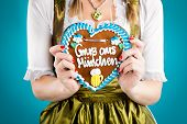 Young woman in traditional Bavarian clothes - dirndl or tracht with a gingerbread souvenir heart