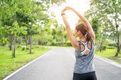Young Female Runner Stretching Arms Before Running At Morning. Women Stretching For Warming Up Befor poster