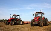 Two Red Tractors With A Harrow