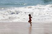 Little Girl Running In The Surf On The Beach