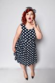 Beautiful Full-length Portrait Of A Red-haired Woman Plus Size In A Polka-dot Retro Dress, Looking W poster