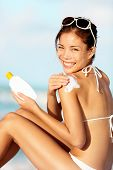 Sunscreen woman. Girl putting sun block on beach holding white sun tan lotion bottle. Beautiful youn