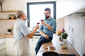 An Adult Hipster Son And Senior Father Indoors In Kitchen At Home, Drinking Wine. poster