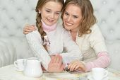 Happy Mother And Daughter Looking At Fingernails While Reading Magazine And Drinking Tea Together poster