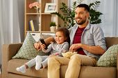 family, fatherhood and people concept - happy father and daughter with popcorn and remote control wa poster