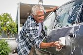 Happy senior man washing car with soap and foam. Old retired man cleaning automobile with sponge in  poster