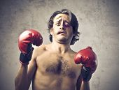 stock photo of pugilistic  - Wounded boxer with tired and frightened expression - JPG