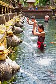 TAMPAK SIRING, BALI, INDONESIA - JANUARY 26: People praying at holy spring water temple Pura Tirtha