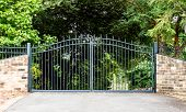 Metal Driveway Property Entrance Gates Set In Brick Fence With Garden Trees  In Background poster