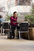 Hispanic Businessman - Telecommuting From Internet Cafe