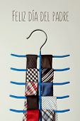 the text feliz dia del padre, happy fathers day written in spanish, and a necktie hanger with some n poster