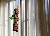 String Puppet Gazing Outside Window In Sun