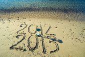 Sand-glass and calendar on a beach