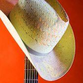 Western Hat On Guitar Neck Isolated Against Orange