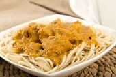 stock photo of ayam  - Dry Curry Mee - Malaysian chicken curry with coconut milk and noodles on a woven mat.