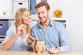 Happy couple putting Euro mony coins in a piggy bank