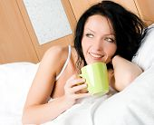Beautiful Brunette Woman With A Cup Of Coffee In Bed