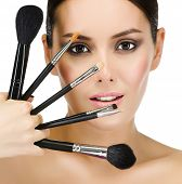 portrait of attractive  caucasian  woman brunette isolated on white studio shot looking at camera face skin makeup closeup brushes