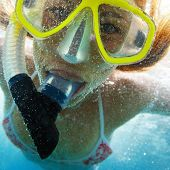 Extreme close up underwater portrait of a woman with snorkeling gear and with a lot of bubbles on fa