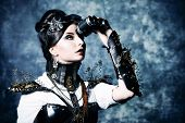 Portrait of a beautiful steampunk woman looking through the binoculars over grunge background.
