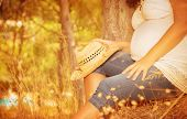 Pregnant girl sitting in autumnal park, body part, tummy of expectant woman, spending time in countr