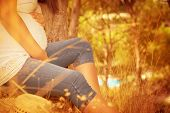 Pregnant female relaxing in autumnal park, sitting down near tree, enjoying autumn nature, body part, sunny day, happy and healthy pregnancy concept