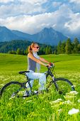 Active woman on bicycle in mountains, beautiful landscape, active lifestyle, riding on pushbike, spo