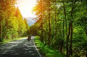 Biker on mountainous road in sunset light, motorcyclist on highway, drive motorbike along Alps, Euro